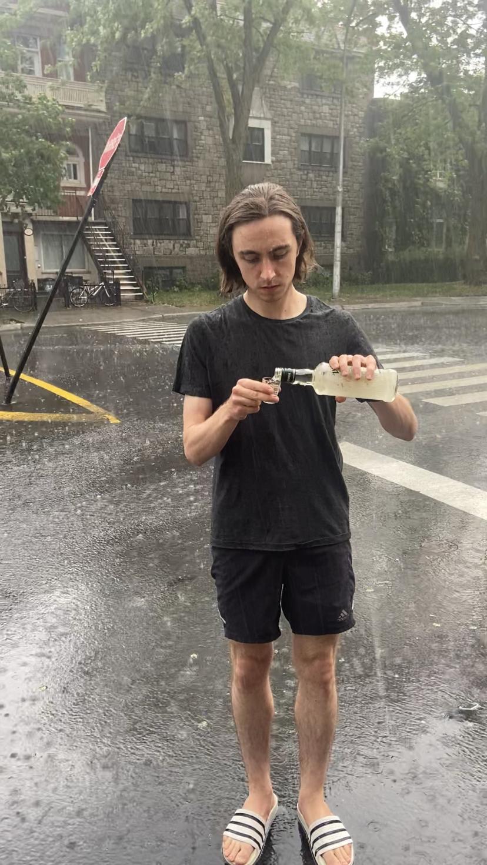 Steve Giasson. Performance invisible n° 44 (Boire de la vodka sous la pluie). Performeur : Jake Laffoley. Crédit photographique : Rachel Dare. 23 juin 2020.