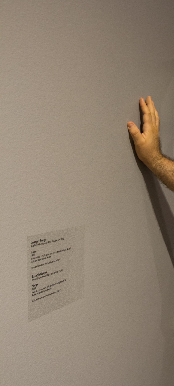 Steve Giasson. Performance invisible n° 8 (Laisser, du bout du doigt, une légère tache de graisse sur le mur d'un lieu d'exposition.) Performeur : Steve Giasson. Crédit photographique : Daniel Roy. Musée des beaux-arts de Montréal, 18 juillet 2015.